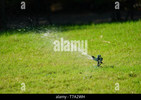 Sprinkler grass working system, working on the field in the garden. - Stock Photo