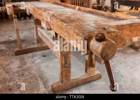 Detail View of wooden vise at a freestanding used workbench. - Stock Photo