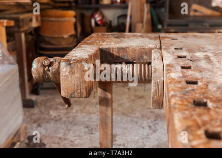 Detail View of wooden vise at a freestanding used bench. - Stock Photo