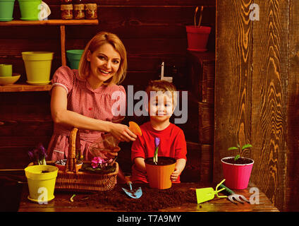 Irrigation concept. Happy family spray spring flower with water for irrigation. Irrigation of houseplant. Drainage and irrigation - Stock Photo