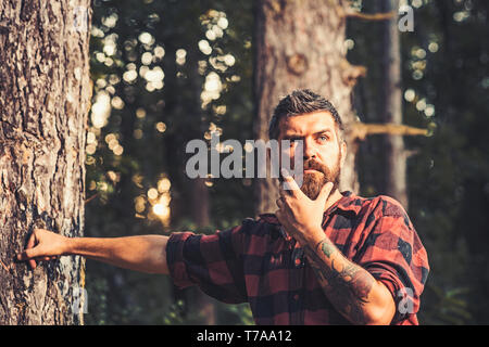 Thoughtful man standing next to tree. Curious lumberjack holding his chin. Hipster wandering in nature - Stock Photo
