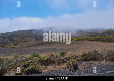volcanic landscape of Haria, Lanzarote, clouds over the volcanic rocks - Stock Photo