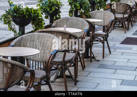Empty chairs and tables in a outdoor restaurant on a cold sunday afternoon. - Stock Photo