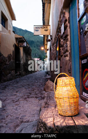 Cobble stone street with lantern sitting on wood stand - Stock Photo
