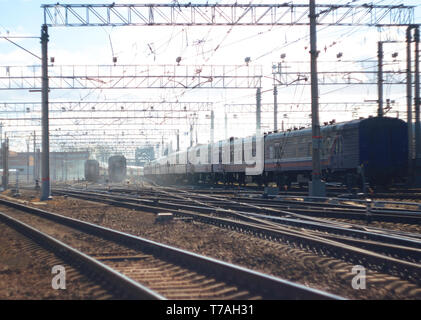 Landscape with the crossing of railway tracks with multiple trains. In the distance everything is lost in the morning fog - Stock Photo