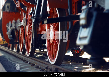 The red wheels of an old vintage steam locomotive, actively used in the 20th century, and now an exhibition model in the Museum. - Stock Photo