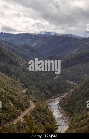 Aerial view of the Feather River Canyon and railroad tracks with storm clouds passing overhead in the sky. - Stock Photo