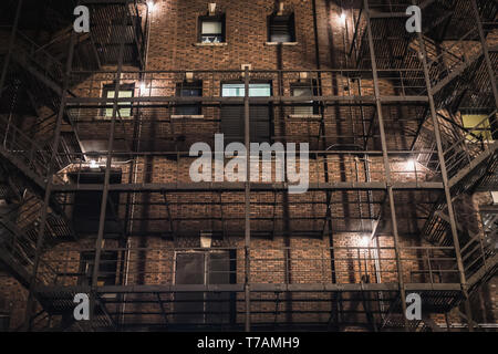 Facade of a typical old New York City building at night in Manhattan - Stock Photo
