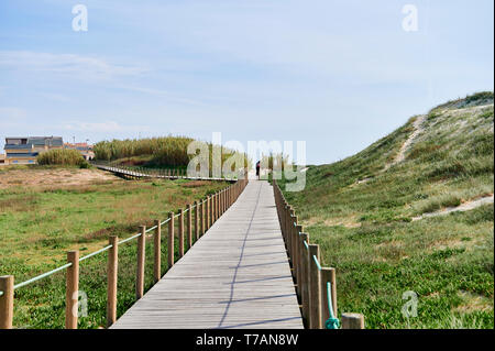 Wooden footwalk over the dunes in portugal near the beach - Stock Photo