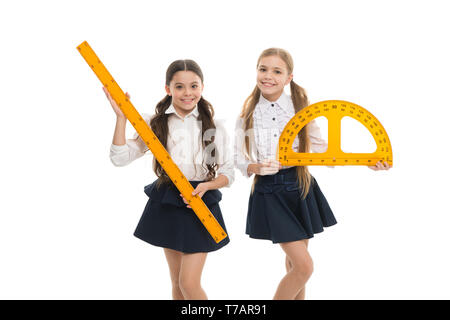 Pupils cute girls with big rulers. Favorite school subject. Education and school concept. School students learning geometry. Kids school uniform isolated white. STEM concept. Draw geometric figures. - Stock Photo