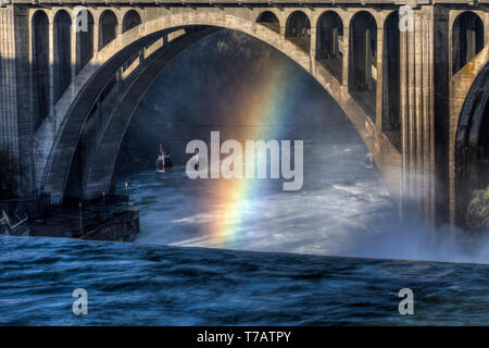 A rainbow appears over Spokane Falls with the Monroe street bridge in the background. - Stock Photo