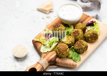 Falafel with yogurt sauce and green salad leaf on wooden serving board. Selective focus. Copy space - Stock Photo