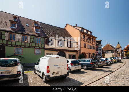 Bergheim, France - 19 Apr 2019: Large group of cars parked in front of the half timbered houses in central Bernheim, Alsace - Stock Photo