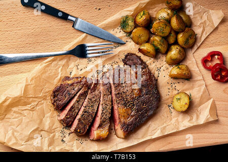 Tasty and fresh, very juicy Ribeye steak from marbled beef on a wooden table with baby potatoes - Stock Photo