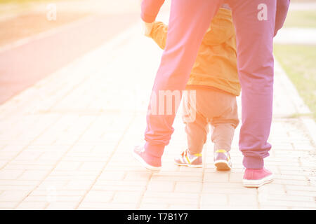 Cute baby boy learning to walk and make his first steps. mom is holding his hand. child's feet close up. view from the back - Stock Photo