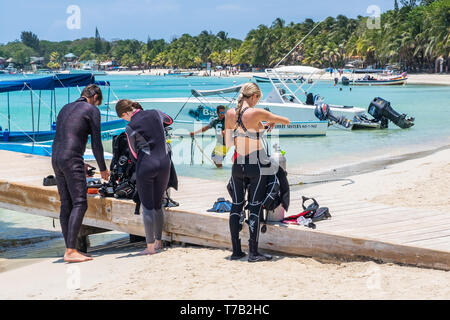 SCUBA enthusiasts prepare to dive on the Mesoamerican Barrier reef off West Bay Roatan Honduras. - Stock Photo