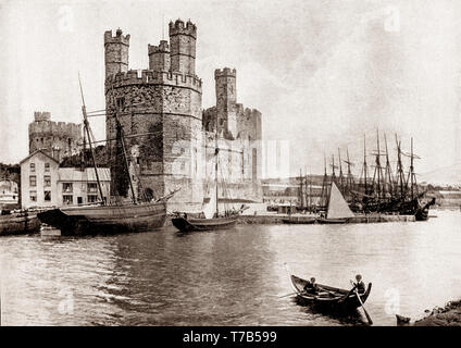 A late 19th Century view of two young boys rowing across the harbour to the  13th Century castle in Caernarfon, royal town and port in Gwynedd, Wales on the eastern shore of the Menai Strait, opposite the Isle of Anglesey. Caernarfon castle, constructed between 1283 and 1330 by order of King Edward I, stands at the mouth of the River Seiont which creates a natural harbour where it flows into the Menai Strait. - Stock Photo