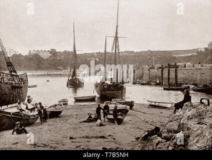A late 19th Century view of  the harbour at Tenby, a walled seaside town in Pembrokeshire, Wales, on the western side of Carmarthen Bay. The town's fortunes rose when a local resident, merchant banker and politician, Sir William Paxton invested heavily in the area. With the growth in saltwater sea-bathing for health purposes, Paxton went on to create a 'fashionable bathing establishment suitable for the highest society. - Stock Photo