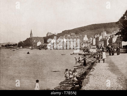 A late 19th Century view of the seafront at Port Bannatyne on the Isle of Bute, Firth of Clyde, Scotland. The village started in 1801 with the building of a small harbour on Kames Bay. Lord Bannatyne of Kames Castle, at the head of the bay, planned the village in an attempt to rival Rothesay. Initially known as Kamesburgh, by the mid-19th century, steamers were calling there regularly. In 1860 the Marquess of Bute purchased this part of the island and renamed the village Port Bannatyne in honour of the long historical association of the Bannatyne family with the area. - Stock Photo