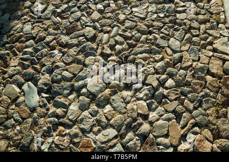 Close-up of rough stone pavement in a pathway, forming a singular background at Marvao. A medieval hamlet perched on a crag in Portugal. - Stock Photo