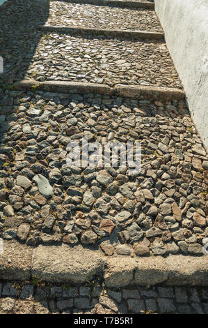 Rough stone pavement in a pathway made of large stairs on sunny day at Marvao. A medieval hamlet perched on a crag in Portugal. - Stock Photo
