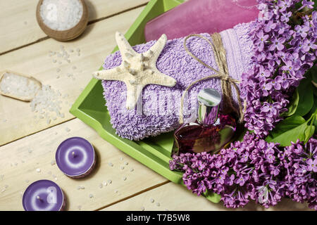 Spa concept with sea salt, perfume, candles, towel and lilac flowers for bath on wooden background. Aromatherapy for relaxation, top view. - Stock Photo