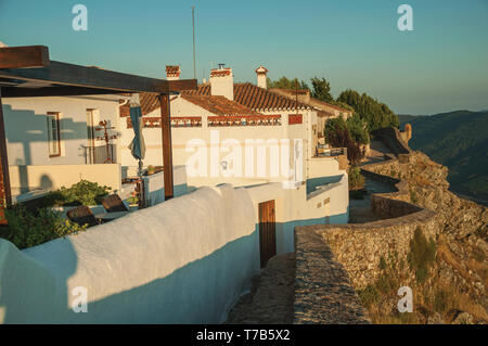Stone wall and white old houses over rocky cliff with hilly landscape on sundown at Marvao. A medieval hamlet perched on a crag in Portugal. - Stock Photo