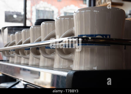Close up a row of clean off white and blue coffee mugs behind a chrome rail. Photographed with a shallow depth of field. - Stock Photo