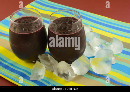 Two cold blueberry smoothie ice drinks in glasses on striped place mat with ice cubes - Stock Photo