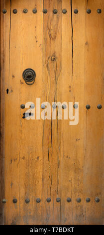 wooden door with wrought iron elements close up. - Stock Photo