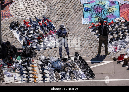 The area of the port is seen occupied by street vendors known as 'the manteros' offering their merchandise, mainly, shoes, bags, glasses, hats. The sale and purchase of products on the street offered by street vendors popularly called 'manteros' is prohibited in Barcelona. Looming municipal elections has revitalized the police effort clear vendors from the street after a long period of permissiveness by the Barcelona City Council.  The new police policy consists of concentrating the 'manteros' in a single area of the port, which is now being oversupplied by vendors. The issue of street vendors - Stock Photo