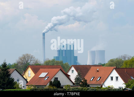 FILED - 27 April 2019, ---: Single-family houses can be seen in front of a lignite-fired power station. The global rate of species extinction is currently ten to one hundred times higher than the average of the past 10 million years and continues to rise, according to the key issues paper presented by the World Biodiversity Council IPBES in Paris on 6 May 2019. For three years, the experts had reviewed 15,000 literature sources and then summarized their findings on 40 frightening pages. At most sites, the number of native species had already fallen by 20 percent. By contrast, the number of peo - Stock Photo