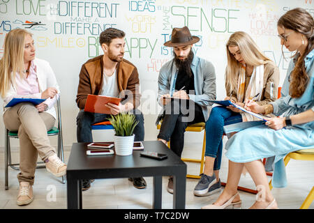 Group of people variously dressed writing some mental test during the psychological training, sitting together in the office - Stock Photo