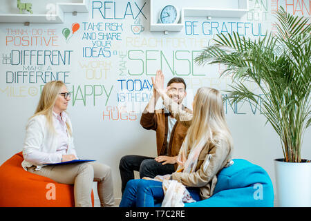 Young and happy couple giving five with hands during the psychological counseling with senior female psychologist in the modern office - Stock Photo