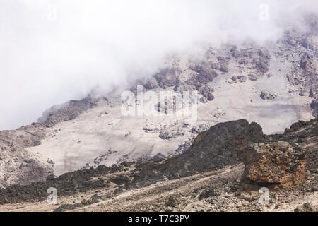 Dense clouds covering sharpen rocks of the mountains. Grey and brown land. Climbing to the top. Extreme adventure. - Stock Photo