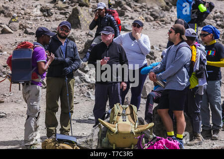 Brave and extreme group of tourists having a rest between long walks and climb to the mountain. Eating or sitting on their bags, tired. Wearing caps - Stock Photo