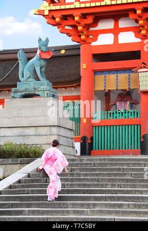 Girl in traditional  japanese clothes of kimono (yukata) climbs the stairs in Fushimi Inari shrine in Kyoto, Japan - Stock Photo