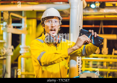 Young man in a yellow work uniform, glasses and helmet in industrial environment,oil Platform or liquefied gas plant looking into his empty wallet. Do - Stock Photo