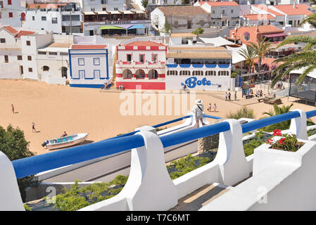 Woman looking to small beach village with colorful houses from terrace - Stock Photo