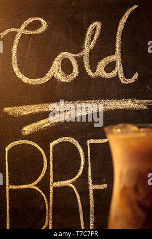 Cold brew coffee with writing on chalk board in background. - Stock Photo