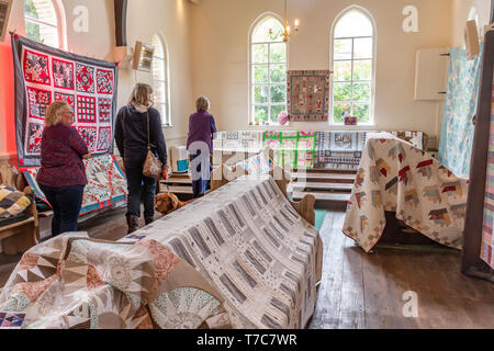 Homemade quilts on display in a village hall at the Oakhanger May