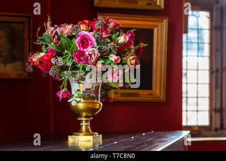 Vase with a beautiful fresh bouquet of flowers in the interior of an ancient palace. Bouquet of flowers in a porcelain vase in vintage style. Renaissa
