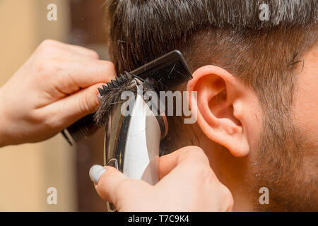 Woman Hairdresser cuts man's hair with electric clipper trimmer - Stock Photo