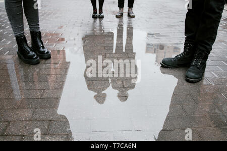 Reflection of a group of people, four pairs of legs and a pair guy and girl in a puddle on the road. - Stock Photo