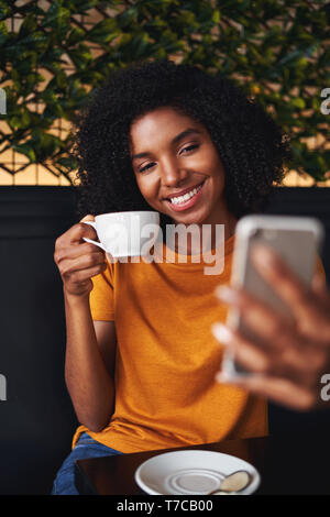 Attractive woman in casual clothing takes selfie in a coffee shop - Stock Photo