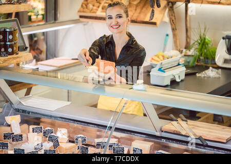 Beautiful woman offering cheese on delicatessen counter - Stock Photo