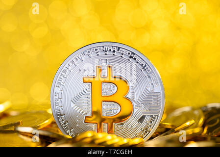 Bitcoin stand in pile on golden coins - Stock Photo