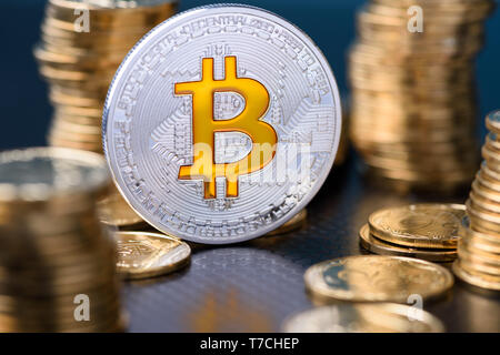 Bitcoin. Silver bitcoin coin between golden coins stacks with reflection. - Stock Photo