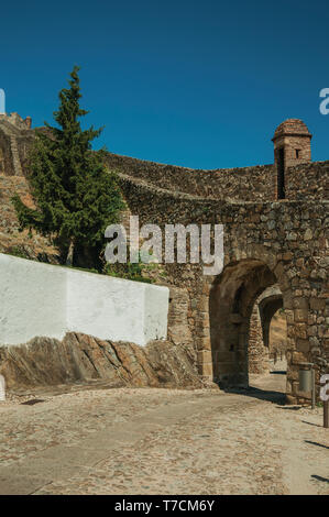 Arched gateway in the city outer wall made of stone with pathway under it and watchtower at Marvao. A medieval hamlet perched on a crag in Portugal. - Stock Photo