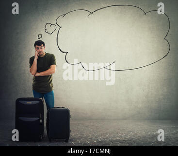 Full length portrait of thoughtful young man traveler standing behind his luggage holding finger to head and waiting. Pensive tourist guy having quest - Stock Photo